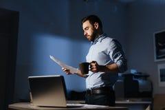 Homem de negócios Working com originais tarde na noite Foto de Stock Royalty Free