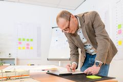Homem de negócios Writing On Notepad na mesa imagens de stock royalty free