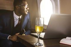 Homem de neg?cios afro-americano atrativo e bem sucedido com funcionamento de vidros em um port?til ao sentar-se na cadeira de fotos de stock royalty free