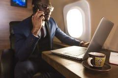 Homem de neg?cios afro-americano atrativo e bem sucedido novo com glassies que fala no telefone e no quando de trabalho imagem de stock royalty free