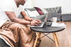 Homem de neg?cios afro-americano novo que trabalha remotamente em casa em um port?til foto de stock royalty free
