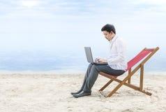 Homem de neg?cios asi?tico que trabalha com o port?til que senta-se na cadeira de praia na praia fotos de stock