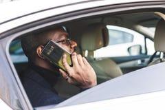 Homem de neg?cios bem sucedido novo que fala no telefone que senta-se no assento traseiro de um carro caro Negocia??es e neg?cio imagens de stock