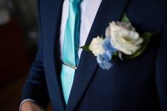 Homem de neg?cios no terno azul que amarra a gravata Equipamento ocasional esperto Homem que come? pronto para o trabalho A manh? imagens de stock