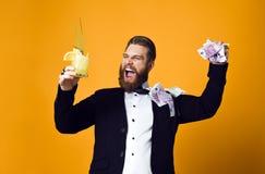 Homem de neg?cios novo feliz com vidro do cocktail na roupa formal que guarda o grupo de c?dulas do dinheiro imagens de stock royalty free