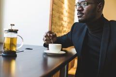 Homem de neg?cios de pele escura consider?vel novo em um caf? com um copo do ch? imagens de stock
