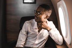 Homem de neg?cios preto afro-americano novo bem sucedido que senta-se na cadeira de seu jato privado fotos de stock royalty free