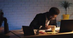 Homem de neg?cios preto novo cansado com o laptop e os pap?is que trabalham no escrit?rio da noite Ele que trabalha com documento filme