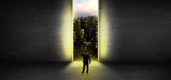 Homem de neg?cios que olha a uma arquitetura da cidade de uma sala vazia escura foto de stock