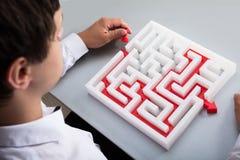 Homem de neg?cios que resolve o labirinto imagem de stock