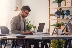 Homem de neg?cios que senta-se em sua mesa de escrit?rio que trabalha em um computador e que usa o computador imagens de stock