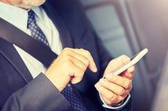 Homem de neg?cios superior que texting no smartphone no carro fotos de stock