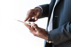 Homem de negócio afro-americano que usa uma tabuleta tátil sobre o branco Imagem de Stock