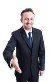 Homem de negócio amigável e sorrindo que inclina-se para a agitação da mão Foto de Stock Royalty Free
