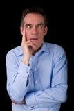 Homem de negócio da Idade Média que puxa cruz engraçada a cara Eyed Fotografia de Stock Royalty Free