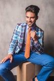 Homem de negócio de sorriso que senta-se em uma caixa de madeira Fotografia de Stock Royalty Free