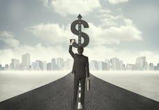 Homem de negócio no título da estrada para um sinal de dólar Foto de Stock Royalty Free