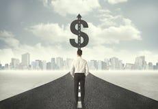 Homem de negócio no título da estrada para um sinal de dólar Fotografia de Stock Royalty Free