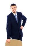 Homem de negócio que está com cadeira do escritório Foto de Stock Royalty Free