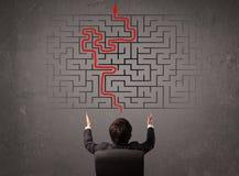 Homem de negócio que olha um labirinto e a maneira para fora Foto de Stock