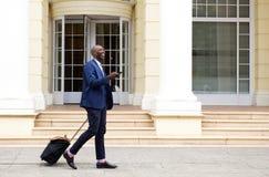 Homem de negócios africano que anda com saco e telefone celular Imagem de Stock