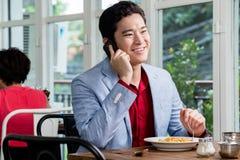 Homem de negócios asiático que fala em seu móbil Imagem de Stock