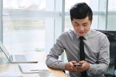 Homem de negócios asiático que texting no smartphone Foto de Stock