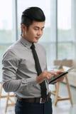 Homem de negócios asiático que usa a tabuleta digital Foto de Stock Royalty Free