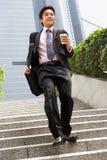 Homem de negócios chinês que apressa-se abaixo das etapas Imagens de Stock Royalty Free