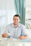 Homem de negócios com calculadora de mão que verific facturas Foto de Stock
