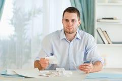 Homem de negócios com calculadora que verific facturas Foto de Stock