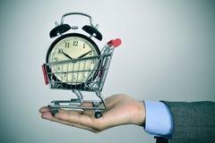 Homem de negócios com um despertador em um carrinho de compras Foto de Stock