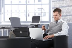 Homem de negócios de sorriso que trabalha no portátil no escritório Foto de Stock Royalty Free