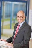 Homem de negócios de sorriso Standing At Podium Imagens de Stock Royalty Free