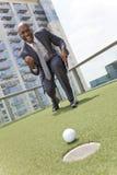 Homem de negócios do americano africano que joga o golfe do telhado Fotografia de Stock Royalty Free