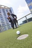 Homem de negócios do americano africano que joga o golfe do telhado Foto de Stock