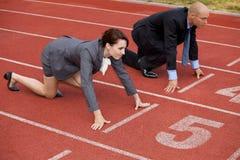 Homem de negócios e mulher na linha do começo de pista de atletismo Fotos de Stock Royalty Free