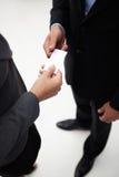Homem de negócios e mulher que trocam um cartão Imagens de Stock