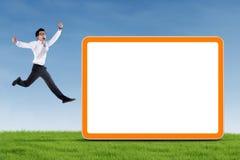 Homem de negócios entusiasmado que salta com placa vazia Imagem de Stock