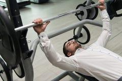 Homem de negócios Exercise Bench Press com Barbell Foto de Stock