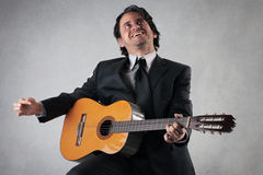 Homem de negócios feliz que joga a guitarra Fotos de Stock