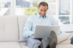 Homem de negócios feliz que usa o portátil com seus pés acima Fotografia de Stock
