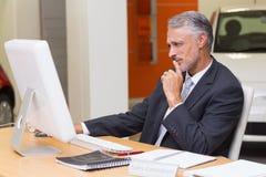 Homem de negócios focalizado que usa seu portátil Imagem de Stock