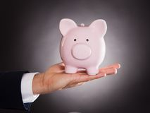 Homem de negócios Holding Piggybank Fotografia de Stock Royalty Free