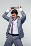 Homem de negócios irritado que despedaça seu portátil Fotografia de Stock
