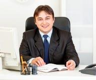 Homem de negócios moderno de sorriso que senta-se na mesa de escritório Imagens de Stock Royalty Free
