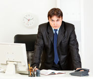 Homem de negócios moderno estrito que está na mesa de escritório Fotografia de Stock