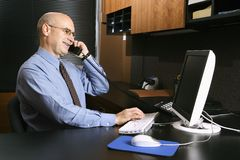 Homem de negócios na mesa no telefone Imagens de Stock Royalty Free