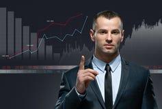 Homem de negócios novo com infochart no fundo preto Fotos de Stock Royalty Free