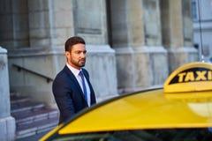 Homem de negócios novo com um táxi Foto de Stock Royalty Free